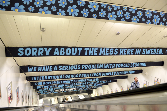 File photo of a man ascending an escalator as signs put up by the Sweden Democrats political party are seen at Ostermalmstorg subway station in Stockholm